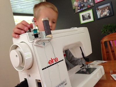 Connor is ready to sew. Maybe a few too many bobbins on the machine there buddy.