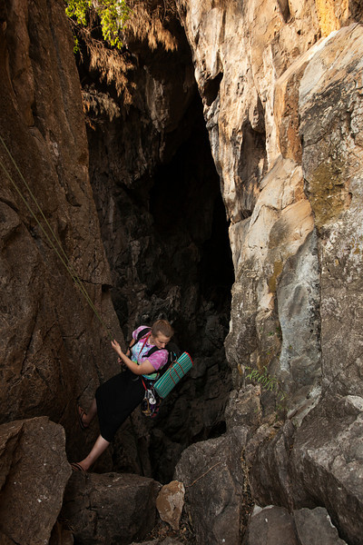 Tracy rappels into a cave at the end of a day of climbing.