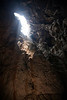 Looking up at the sky shining through the massive opening of a large cave after rappelling down into the mouth.