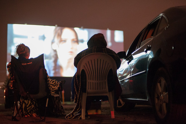 "131121 Hunger Games JOED VIERA/STAFF PHOTOGRAPHER Lockport, NY- Nicole McKeone and Brian Mancuso watch ""The Hunger Games"" outside of their car at the Transit Drive-In Theater on Thursday Nov 21st, 2013."
