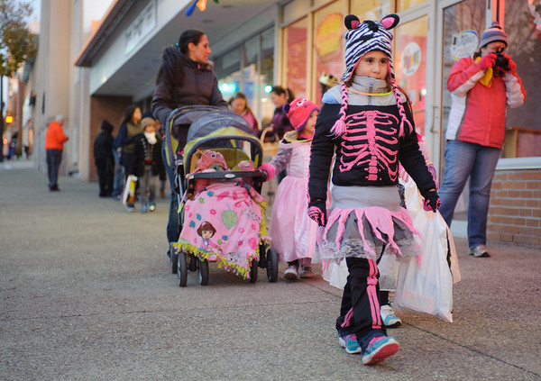 131025 Halloween JOED VIERA/STAFF PHOTOGRAPHER Lockport, NY- Mya Dietz (7) dressed as a Zebra Skeleton walks down Main street in search of treats on Friday October 25th, 2013.