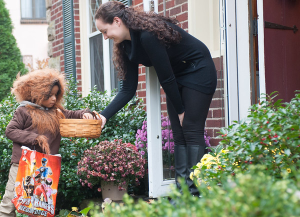 131030 trick-or-treating JOED VIERA/STAFF PHOTOGRAPHER Lockport, NY-Trick or Treater Jeter Serano dressed as a wolfman grabs candy for his bag from Kelsie Bragg at her home on Thursday Oct 31st, 2013.