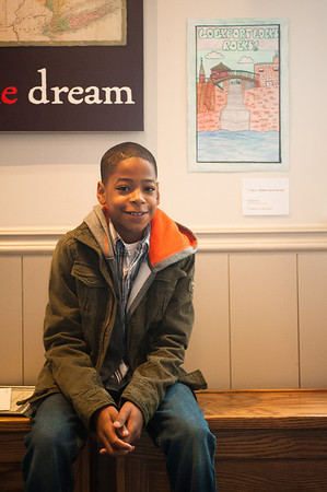131026 Canal Aniversary JOED VIERA/STAFF PHOTOGRAPHER Lockport, NY- Caleb Harris (12) a 7th grader at Gaskill Prep School and winner of the Erie Canal Discovery Center poster contest sits in front of his award winning poster at the ECDC on Saturday October 26th, 2013.