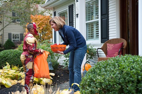 131030 trick-or-treating JOED VIERA/STAFF PHOTOGRAPHER Lockport, NY-Anne McCafferey gives out candy to trick or treater Jared Donelson dressed as Iron-man at her home on Thursday Oct 31st, 2013.