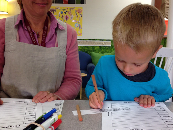 Connor practicing writing his name with Teacher Cathy