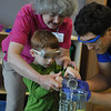 "Villard Djemson (Salisbury, Md.), Chrystian Banuelos (Pomona, Calif.), and Marisa Maher (Edmond, Okla.) put on a science demonstration for York General Childcare.<br /> In this picture Mason volunteers to help with the ""Christmas tree"" experiment."