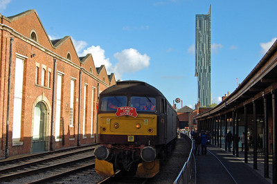 The Beetham Tower dominates the skyline as 47760 is pictured alongside the world's oldest railway station - Liverpool Road - which was the original terminus of the Liverpool & Manchester Railway (03/11/22013)