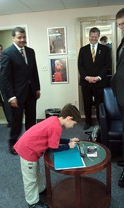 As Rep. Randy Hultgren (@RepHultgren) and @josephgruber look on, Neil deGrasse Tyson (@neiltyson) asks @AgilistaAG's son, Aidan, to inscribe the book Skippyjon Jones: Lost in Spice, which Aidan presented him as a gift