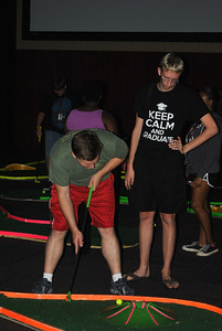 Students try their hand at glow in the dark mini golf.