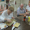 Cannon Inn resident Carolyn Hammond takes her turn at placing cookie dough in a baking pan. One of those watching, to the far right, is resident George E. Williams. On the 12th anniversary of the Sept. 11 attacks, residents made a card and baked cookies for firefighters at the Terre Haute Fire Department Station 7.