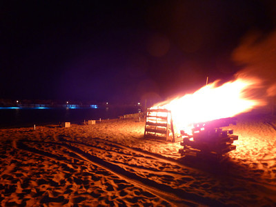 At night they often light a beach fire. The stone pier in the background has blue underwater lights...