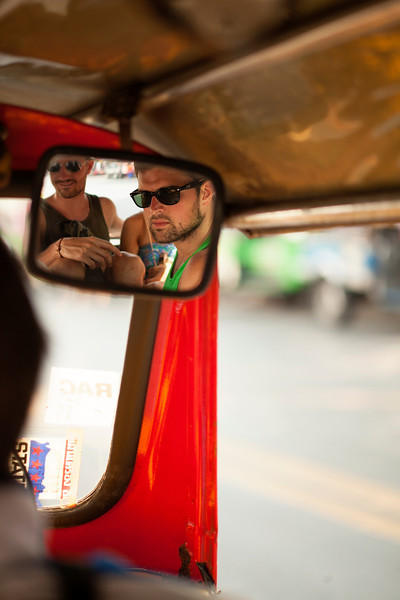 Paul and Eric watch the Bangkok streets fly by from the back of a tuk-tuk.