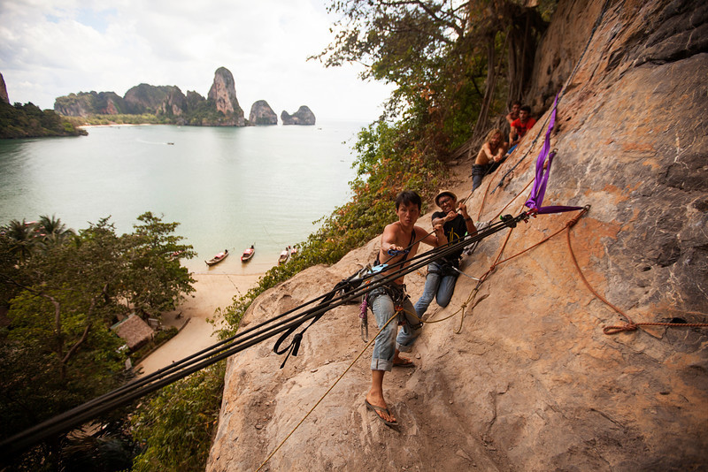 Highliners get together to tension the line, with Tonsai Beach down below.