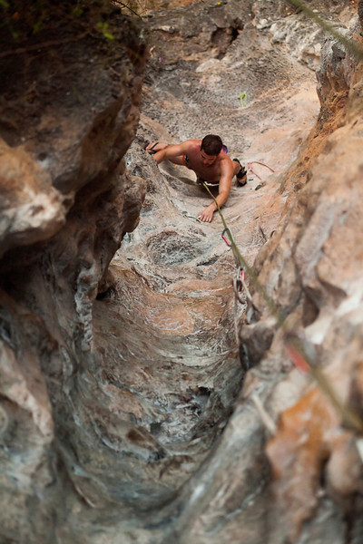 Paul climbs into the tube on <i>Groove Tube 6a</i> on the Fire Wall at Tonsai Beach.