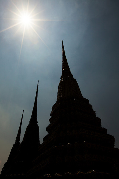 Temple towers rise into the sky under a hot Thai sun.