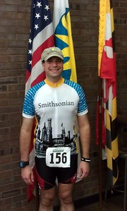 Craig poses with the flag of the United States (l), flag of the Smithsonian Institution, and flag of Maryland