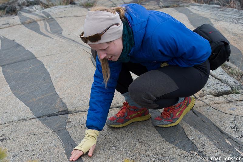 Katrin som är inbiten klättrare kollar greppet i berget.