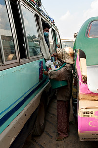 A lady selling goods to a van full of people and stuff on the Mekong.
