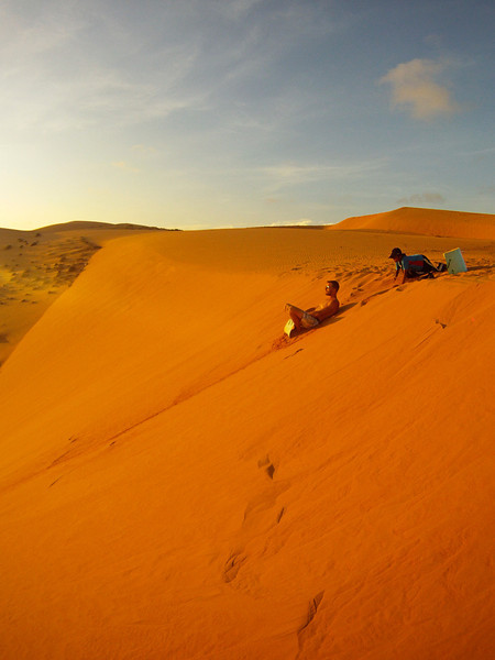 Eric takes a ride on a local attraction, sledding down the red sand dunes at sunset.