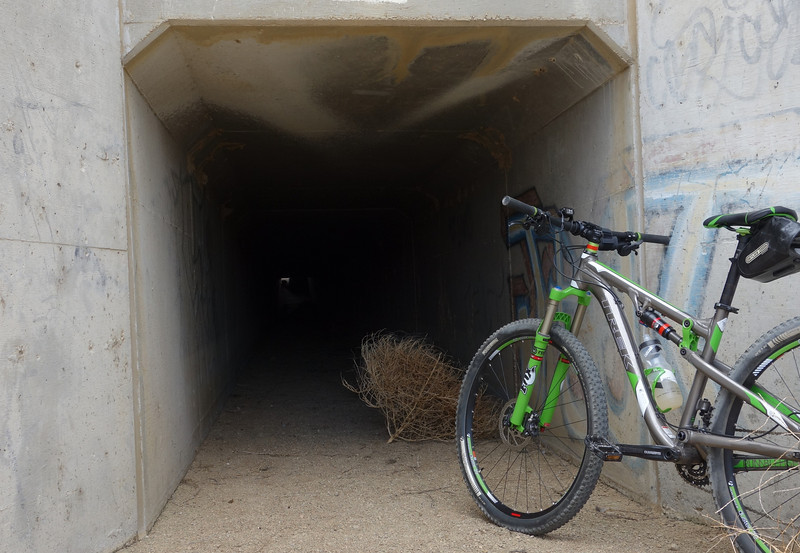This tunnel goes UNDER the aqueduct.  And I've confirmed that it IS free of dead bodies and homeless people. :)  Surprisingly, I didn't spot a single piece of trash in there.  There's some obvious graffiti, but otherwise it's just a cool little tunnel filled with lots of tumbleweed.