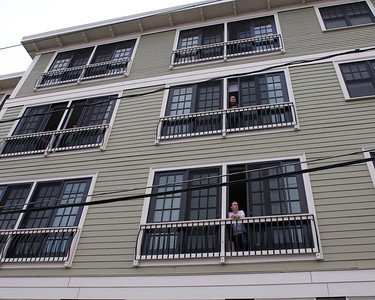 041913, Cambridge, MA - Residents of a condo complex on Webster Street look out their windows down Norfolk Street where the Boston Marathon bombing suspects allegedly live. Photo by Ryan Hutton