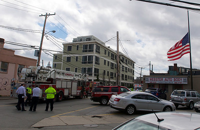 041913, Cambridge, MA - An American flag flies at half mast at the intersection of Webster and Prospect Streets as first responders gather nearby a fire truck. Photo by Ryan Hutton