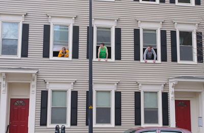 041913, Cambridge, MA - Residents of Cambridge Street lean out their window to see what is going on down the street at Norfolk Street. Photo by Ryan Hutton