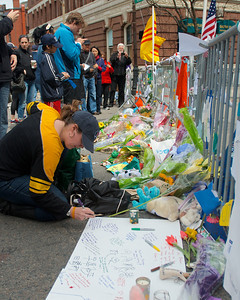 042013, Boston, MA - Pedestrians stop to write notes, take pictures and leave flowers at the makeshift memorial on Boylston Street, which has been closed since Monday's attack on the Boston Marathon. Photo by Ryan Hutton