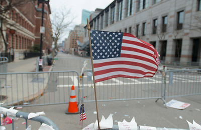 042013, Boston, MA - An American flag flies from the barricade set up to block off Boylston Street while the investigation into the bombing of the Boston Marathon last Monday continues. Photo by Ryan Hutton