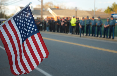 042013, Wilmington, MA - American flags and police officers from all over the state line the street as hundreds of people await the arrival of the hearse carrying the body of fallen MIT police officer Sean Collier. Photo by Ryan Hutton
