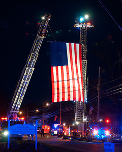 042013, Wilmington, MA - Wilmington Fire trucks display an enormous American flag  for the candle light vigil on the Wilmington town common for fallen MIT police officer Sean Collier. Photo by Ryan Hutton