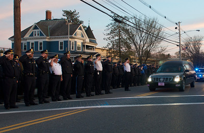 042013, Wilmington, MA - Police officers from all over the state salute the arrival of the hearse carrying the body of fallen MIT police officer Sean Collier. Photo by Ryan Hutton