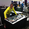2012 and 2013 RESESS intern Nathan Mathabane ready to distribute RESESS calendars  at the UNAVCO booth at the 2013 annual Fall Meeting of the American Geophysical Union in San Francisco, Calif. (Photo/Beth Bartel)