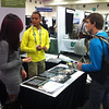 2013 RESESS intern Amanda Labrado and 2012 and 2013 RESESS intern Nathan Mathabane talk about the RESESS program at the UNAVCO booth at the 2013 annual Fall Meeting of the American Geophysical Union in San Francisco, Calif. (Photo/Beth Bartel)