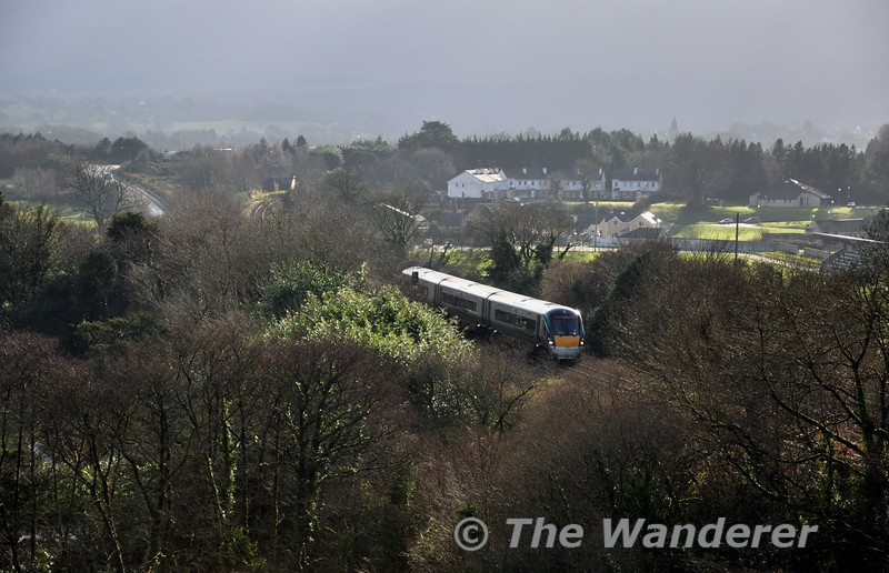 22018 climbs out of Killarney past the townland of Coolcorcoran with the 1130 Mallow - Tralee. This picture was taken from the Old Kilcummin Cemetery which is beside the Three Arch Bridge. It is only possible to obtain this photo in winter months due to the lack of leaves on the trees surrounding the railway line. Sat 12.01.13