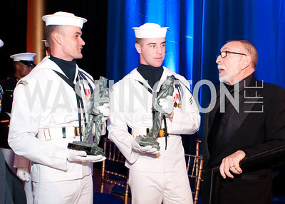 Two young Navy servicemen are given directions about handing off the awards