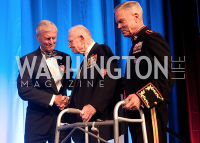 General P.X Kelley shakes John Totushek's hand while being escorted by General James F. Amos