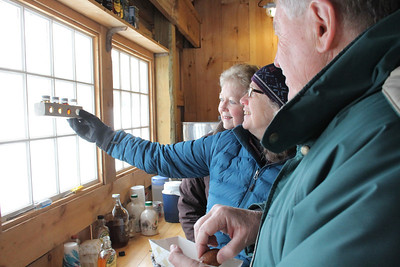 IMG_3493 JPG ed and judy savarese of west windsor look at syrup grading kit held by mary McCuaig at top acres farm in south woodstock