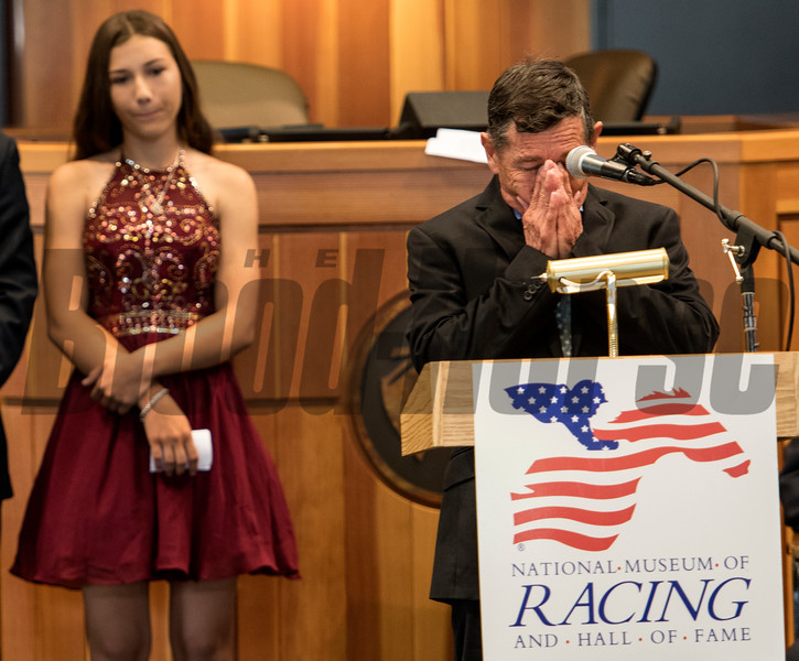 Overcome by emotion, Louie Gomez, father of the late jockey Garrett Gomez gives the acceptance speech for his son as his grand daughter Amanda Gomez looks on at the National Museum of Racing and Hall of Fame induction ceremony held Aug. 4, 2017 at the Fasig Tipton auditorium in Saratoga Springs, N.Y. <br /> Photo by Skip Dickstein
