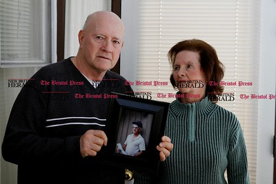 Kevin Bartram | Staff Norman LaFontaine and his sister Terry Dubuc are shown with a photograph of their brother, Pete LaFontaine, at Norman's home in New Britain on Tuesday. Pete LaFontaine was murdered and the case has not been resolved.