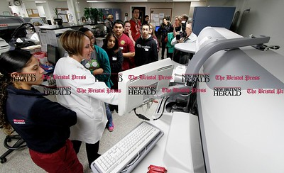Kevin Bartram | Staff Senior medical technologist Mary Mroczek, second from left, demonstrates lab equipment at the Hospital of Central Connecticut on Tuesday. Students in New Britain High School's Health Care Science II class toured several departments at the Hospital of Central Connecticut on Tuesday. Students in the program visit hospitals to help them become workplace ready and to give them real world experience according to teacher Michael Zayas.