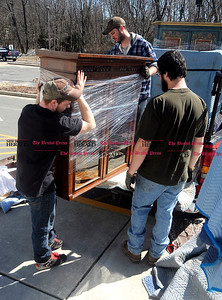 4/1/2014 Mike Orazzi | Staff Tim's Auctions' Bryant Maddox, John Brennan and Ralph Schuster move auction items into the Lyceum while preparing for the 22nd Annual Cabin Fever Auction Sunday. Tim's is also celebrating their 35th year.
