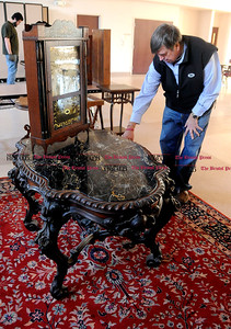 4/1/2014 Mike Orazzi   Staff Tim's Auctions' Tim Chapulis looks over a rosewood table and a Silas Hoadley clock while moving auction items into the Lyceum in preparation for the 22nd Annual Cabin Fever Auction Sunday. Tim's is also celebrating their 35th year.