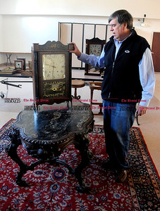 4/1/2014 Mike Orazzi | Staff Tim's Auctions' Tim Chapulis looks over a rosewood table and a Silas Hoadley clock while moving auction items into the Lyceum in preparation for the 22nd Annual Cabin Fever Auction Sunday. Tim's is also celebrating their 35th year.