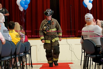 Kevin Bartram | Staff Newington Volunteer Fire Department Lt. Alex Foster models his uniform during a uniform fashion show at the Newington Senior and Disabled Center on Friday. Newington police officer Tim Buggee served as emcee for the event where he urged seniors to become familiar with the uniforms of public safety and utility workers who may visit their homes.