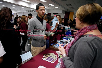 Kevin Bartram | Staff Brandon Calez talks to Cindy Ryan of the Connecticut Center for Massage Therapy during the New Britain High School Academy of Finance and Health Academy Career Fair on Tuesday at the school.