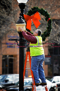 Kevin Bartram | Staff New Britain city worker George Cote repairs a light in Central Park Monday morning. Holiday decorations were recently installed in downtown New Britain and the city's official tree lighting ceremony is scheduled for Tuesday evening.