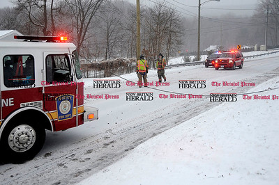 1/2/2014 Mike Orazzi | Staff Bristol firefighters on scene of a one car crash into a utility pole with wires down on Wolcott Avenue at the start of Winter Storm Hercules on Thursday afternoon.