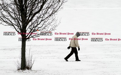 Kevin Bartram | Staff Gene Sarra walks around the lake at Stanley Quarter Park as snow falls on Thursday in New Britain. Sarra makes four laps around the park every day.