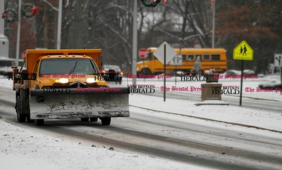 Kevin Bartram | Staff Plows and school buses take to the streets as snow falls on Thursday in Bristol.